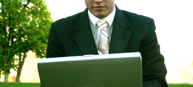 Podnikatel s notebookem na klíně sedí v parku, není mu vidět do obličeje
